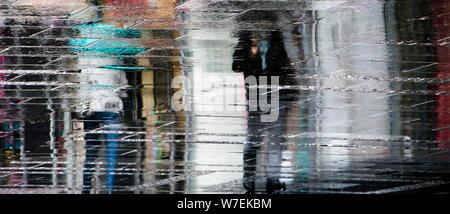 Sfocata riflessione ombra sagome delle persone che camminano sotto ombrellone in una piovosa città pedonale strada bagnata in una pozza