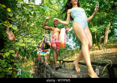 Gruppo di happy amici divertendosi mentre è in esecuzione per nuotare sul fiume. Gioiosa di donne e di uomini in costume da bagno con anelli di gomma al Riverside nella giornata di sole. Estate, amicizia, resort, relazioni concetto. Foto Stock