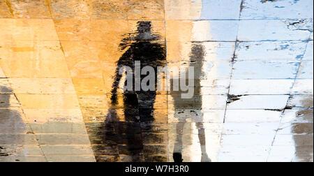 Sfocata riflessione ombra sagome di un uomo e di un ragazzo a camminare su una strada bagnata su una soleggiata giornata estiva nella città vecchia pavimentazione di pietra