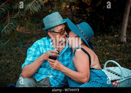 Coppia senior kissing mentre si beve vino insieme a un picnic nel parco