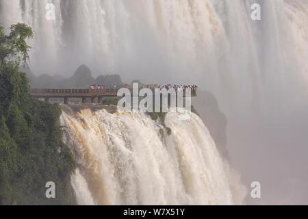 Cascate di Iguazu e turisti sulla piattaforma di osservazione, Iguazu Falls, Parco Nazionale di Iguazu, Brasile, gennaio 2014. Foto Stock