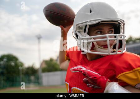 Foto del giocatore di football americano donna gettando la sfera Foto Stock
