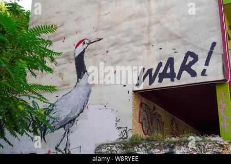 Atene, Grecia, Graffiti di grigio di una gru e la parola guerra su una parete di un vecchio e abbandonato edificio fatiscente Foto Stock