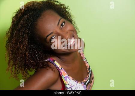 Bella americano africano donna che guarda la fotocamera nella parte anteriore di un muro verde Foto Stock