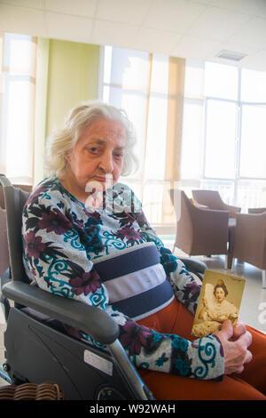Vecchia donna in una casa di cura, tenendo il suo ritratto della gioventù. Foto Stock