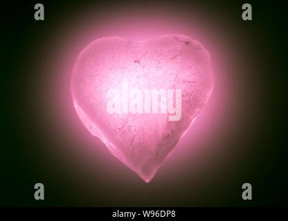 Ghiaccio il simbolo del cuore morbido di colore rosa close-up incandescente nel buio. Texture di ghiaccio con bolle. Foto Stock
