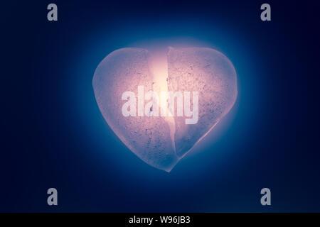 Ghiaccio rotto in metà cuore simbolo di un colore rosso vivo close-up risplende nelle tenebre. Vecchio stile vintage. Texture di ghiaccio con bolle. Simbolo Foto Stock