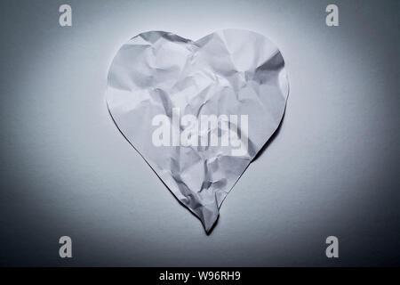 Il simbolo del cuore di fatto dal vecchio, carta sgualcita su un bianco sfondo vintage. Simbolo di un cuore spezzato, amore infelice. Foto Stock