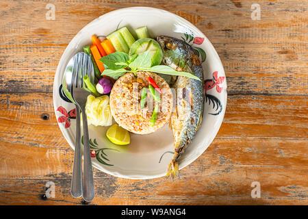 Riso fritto con peperoncino piccante con pesce e verdure in piastra bianca sul tavolo di legno. Foto Stock