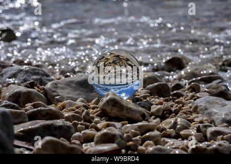 Concetto di estate/ sfera di cristallo del whit della riflessione sul mare in spiaggia