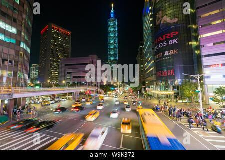 Il traffico nella parte anteriore del Taipei 101 in corrispondenza di un centro occupato intersezione nel distretto di Xinyi, Taipei, Taiwan, Asia Foto Stock