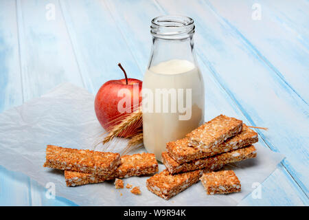 Muesliriegel, Apfel und Flasche mit Milch, Powerriegel Foto Stock