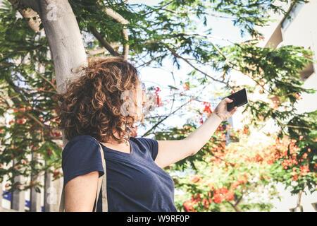 Giovane donna prendendo selfie con lo smartphone al di fuori della città. Ragazza alla moda gioca la realizzazione di nuovi trend storia video con il telefono cellulare sotto alberi in fiore.