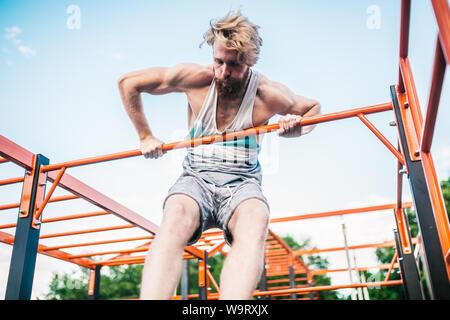 atleta forte che fa tirare-in su sulla barra orizzontale. Uomo muscolare che fa tirare su barra orizzontale in parco. Palestra Bar durante l'allenamento. Allenamento Foto Stock