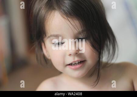 Ritratto di un bel po' di sorridente ragazza con capelli lunghi marrone e lo sguardo verso il basso Foto Stock