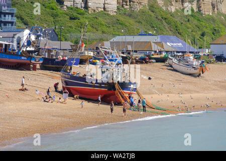 Hastings barca da pesca che viene tirata in alto sulla Città Vecchia Stade barca da pesca beach, persone guardando scartato granchi catturati nelle reti da pesca, East Sussex, Foto Stock