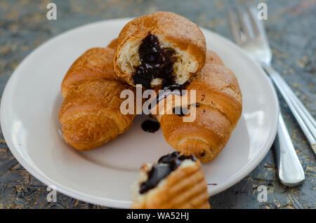 Gustosi croissant burroso sul vecchio tavolo in legno. Foto Stock