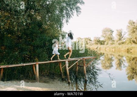 Madre e figlia sono in esecuzione e divertirsi su un ponte di legno su sfondo del fiume e canne. Foto Stock