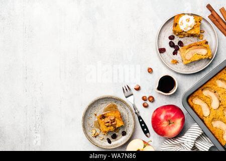 Apple Spice di zucca torta tagliata in quadrati. Sul cemento grigio sfondo a trama. Vista dall'alto. Autunno Comfort Food ricetta torta Foto Stock