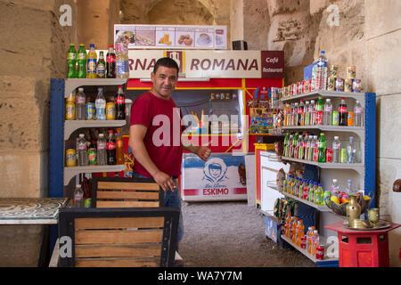 Cafe e ristorante nel famoso anfiteatro rumeno El inceppamento in Tunisia, Africa e Arabian proprietario con il pollice fino e sigaretta in mano Foto Stock