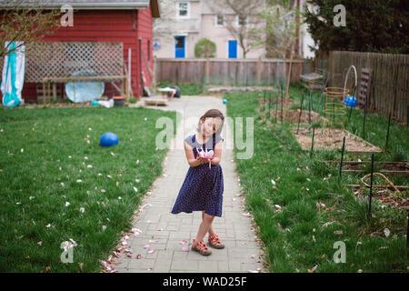 Una bambina si ammira un grande fiore rosa nelle sue mani Foto Stock
