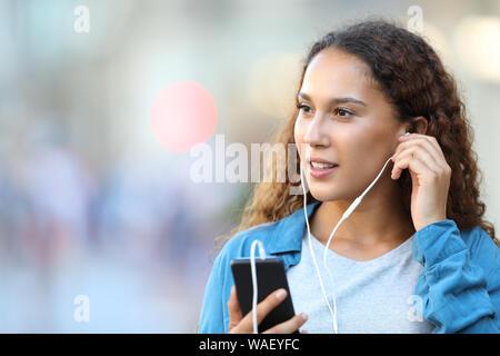 Razza mista donna azienda smart phone mettere gli auricolari per ascoltare musica guardando il lato a piedi in strada Foto Stock