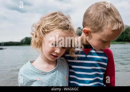 Fratello e Sorella di coccole ogni altro mentre gioco in spiaggia Foto Stock