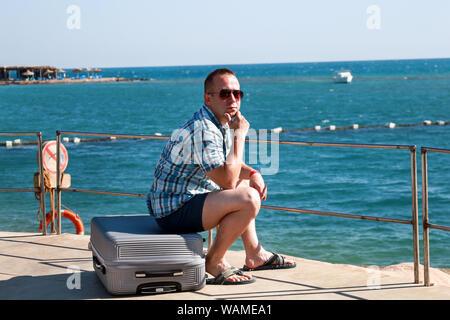 Turisti e viaggiatori è seduto sul suo percorso valigia sulla spiaggia del resort hotel, gode di vista sul mare ambiente, natura paesaggio, panorama, orizzonte.