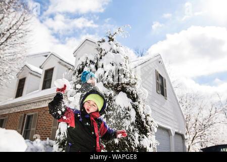 Ragazzo circondato dalla neve sempre colpito con palla di neve da dietro da ragazzo Foto Stock
