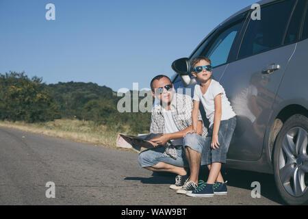 Felice il padre e il figlio in piedi vicino la vettura al giorno. Essi guardare fuori dalla finestra. Le persone aventi il divertimento all'aperto. Concetto di famiglia è pronto per t Foto Stock