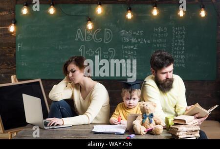 I genitori sulle facce di occupato non si cura di educazione dei loro figlio. Genitori impegnati concetto. Padre libro lettura, madre opera su laptop, sulla lavagna Foto Stock