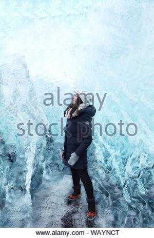 Donna in piedi all'interno della caverna di ghiaccio Foto Stock