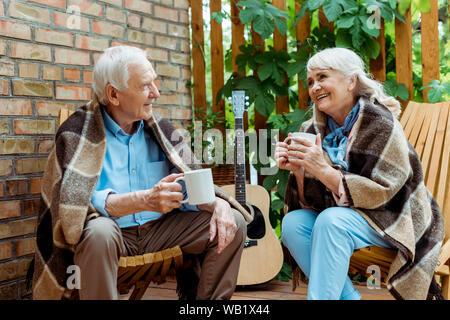 Felice l'uomo senior guardando allegro moglie coppa di ritegno con tè Foto Stock