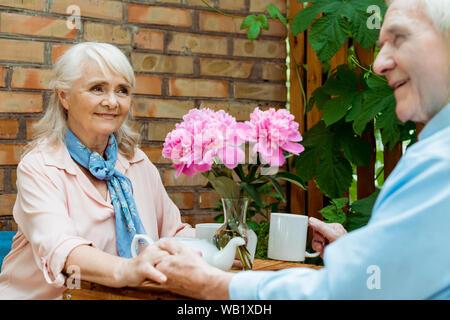 Messa a fuoco selettiva di felice pensionato donna tenendo le mani con allegro senior marito Foto Stock