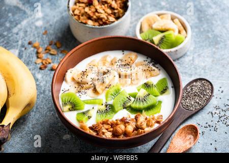 Muesli frutta yogurt ciotola con semi di chia per una sana colazione o uno spuntino. Kiwi, banana, oat granola e lo yogurt greco miscelati in un recipiente. Cibo sano