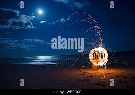La masterizzazione di lana di acciaio fuochi d' artificio sulla spiaggia di notte Foto Stock