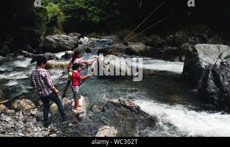 Famiglia di pesca nel ruscello di montagna