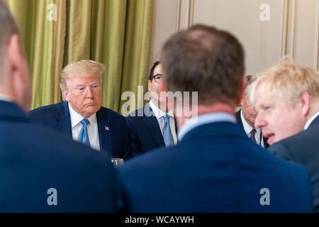 Stati Uniti Presidente Donald Trump, sinistra, durante una colazione di lavoro con il Primo Ministro britannico Boris Johnson, destra e le loro delegazioni a margine del vertice del G7 l'Hotel du Palais Biarritz Agosto 25, 2019 a Biarritz, Francia.