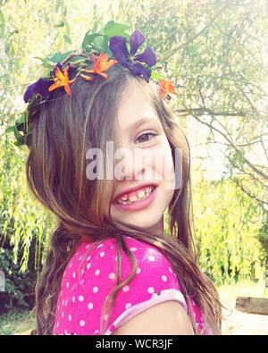 Close-up ritratto di sorridente ragazza carina indossando ghirlanda di fiori