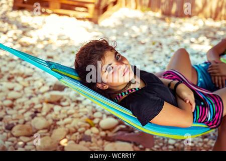 Bambina di refrigerazione in amaca sulla spiaggia, con il piacere di trascorrere del tempo vicino al mare, godendo di felice attivo vacanze estive Foto Stock