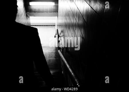 Silhouette uomo a camminare sui passi nel tunnel