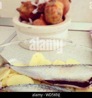 Close-up di sgombro con fette di patate nella piastra sulla tavola Foto Stock