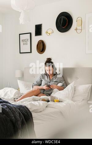 Giovane donna utilizzando smart phone nel letto Foto Stock