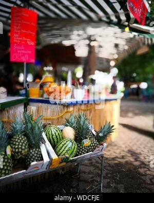 Ananassi e angurie in casse per la vendita al mercato di strada Foto Stock