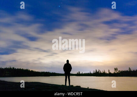 Silhouette di donna in piedi dal lago al tramonto Foto Stock