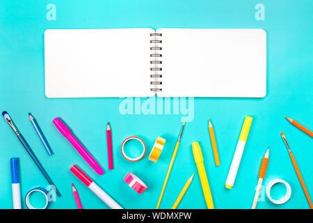Gli elementi della scuola come un telaio su sfondo blu. Colori alla moda, piatto stile di laici. Si torna a scuola concetto. Foto Stock