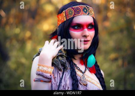 Giovane donna in abiti tradizionali che trasportano tartaruga in foresta Foto Stock