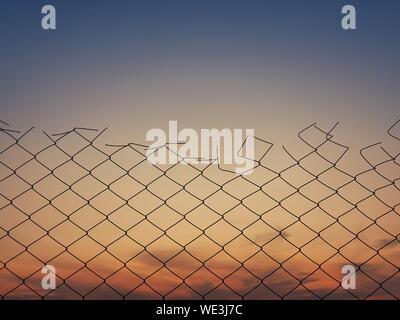 Vecchia maglia di filo di trama di recinzione contro il Cielo di tramonto sullo sfondo.