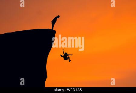 Silhouette Uomo che guarda la donna caduta dal dirupo contro il chiaro cielo arancione