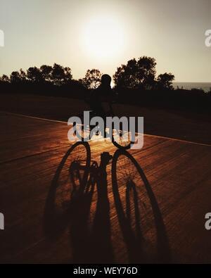Silhouette Boy Bicicletta Equitazione sulla strada contro il cielo chiaro Foto Stock